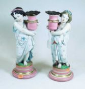 A pair of late Victorian figural porcelain candlesticks, each in the form of a child holding a