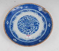 A large Chinese stoneware blue & white charger the centre glazed with a dragon amidst clouds