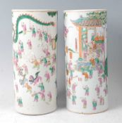 A pair of Chinese famille rose cylindrical vases, each decorated in bright enamels with ceremonial