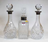 A pair of modern cut glass decanters and stoppers, each of pear shape with silver collar; together
