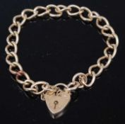 A 9ct gold curb link bracelet with heart shaped padlock clasp and safety chain, 15.7gCondition