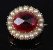 A yellow metal oval cluster brooch, having a centre oval red paste stone measuring approx 11.6 x