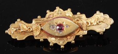 A late Victorian Etruscan style 9ct gold memorial brooch, having a centre navette shaped panel set