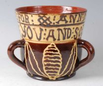 A Wrotham style brown and yellow slipware tyg, the frieze bearing motto 'THIS CUP I MADE FOR ANN