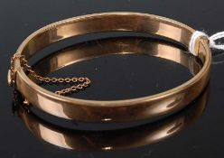 A gilt metal half engraved oval hinged bangle, having box clasp and safety chain, width 8.0mm,