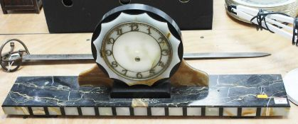 An Art Deco marble cased mantel clock, the raised brass dial with Arabic numerals on a veined