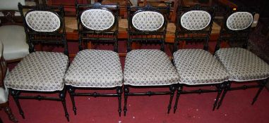 A set of six circa 1900 ebonised and upholstered pad back and seat parlour side chairs