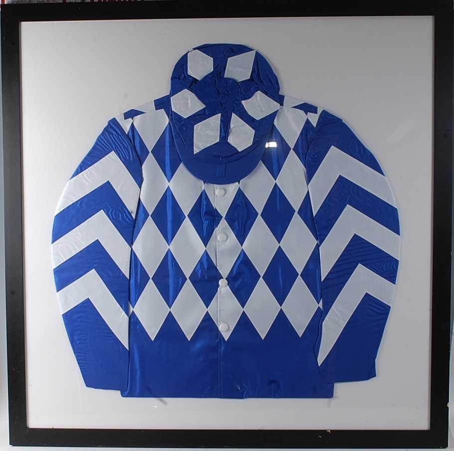 A framed set of jockey silks in blue and white diamond check pattern, 99 x 99cm.