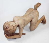 An Eastern carved hardwood figure of a nude woman, shown on all fours, h.22cm