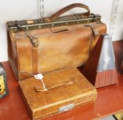A tan leather Gladstone bag; together with a late 20th century metronome; and a tan leather clad