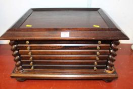 A 20th century stained beech coin collector's cabinet, the six long drawers flanked by barley