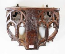 A Victorian carved oak wall bracket, the apron with pierced early English Gothic style carved