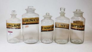 A collection of five various 19th century clear glass apothecary jars and stoppers, each bearing a