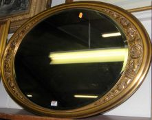 A reproduction gilt framed and bevelled oval wall mirror, 88 x 62cm
