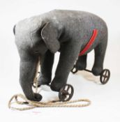 An early 20th century Steiff pull-along elephant, in grey felt, with glass eyes and button to ear,