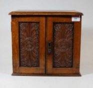 An Edwardian oak smokers cabinet, having a hinged lid above a pair of panelled doors, opening to