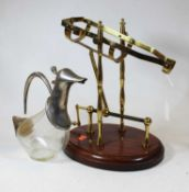 A brass framed decanting cradle with rotating action on a mahogany plinth, together with a novelty