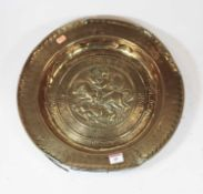 A 19th century copper charger, the centre relief decorated with a figure on horseback, within an