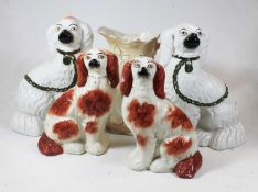 A pair of Staffordshire seated spaniels, on a plain white ground with green padlock and chain;