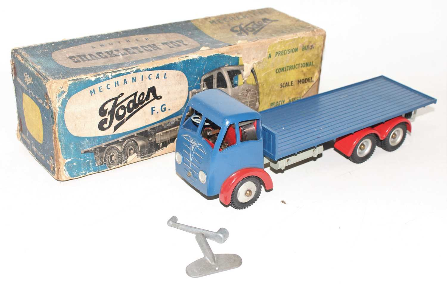 A Shackleton Toys clockwork model of a Foden FG flat bed truck comprising of dark blue cab and