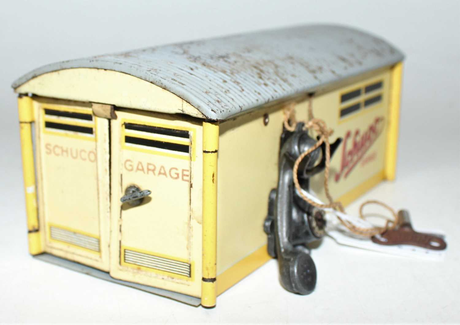 "A Schuco vintage tinplate clockwork car in a garage ""Kommando Anno 2000"" circa mid 40s complete with"