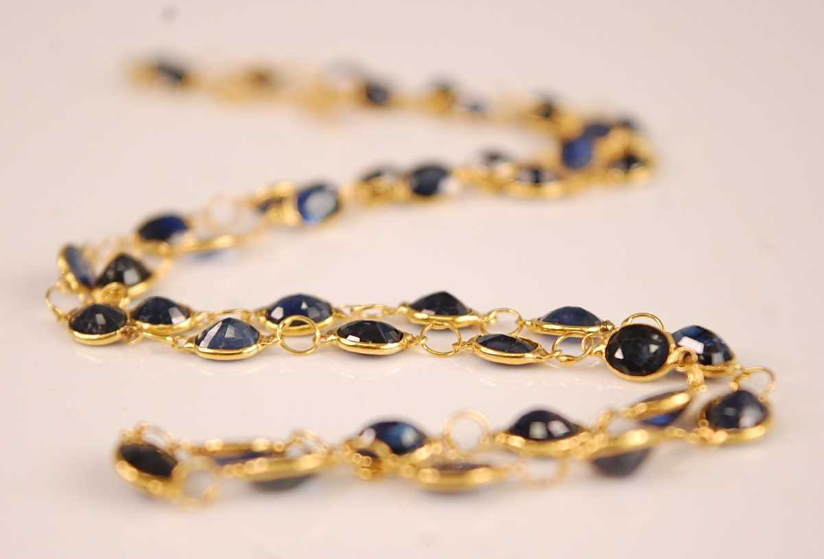 A contemporary yellow metal sapphire set necklace, arranged as 42 oval cut sapphires, each