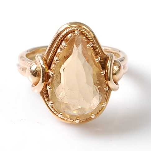 A yellow metal citrine dress ring, featuring a pear cut citrine in a claw setting, with stirrup