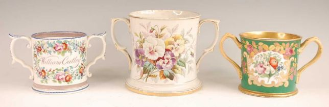 A Victorian soft-paste porcelain loving cup, enamel decorated with a floral reserve within gilt