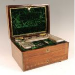 A Victorian rosewood and brass bound fitted toilet box, the hinge cover opening to reveal velvet