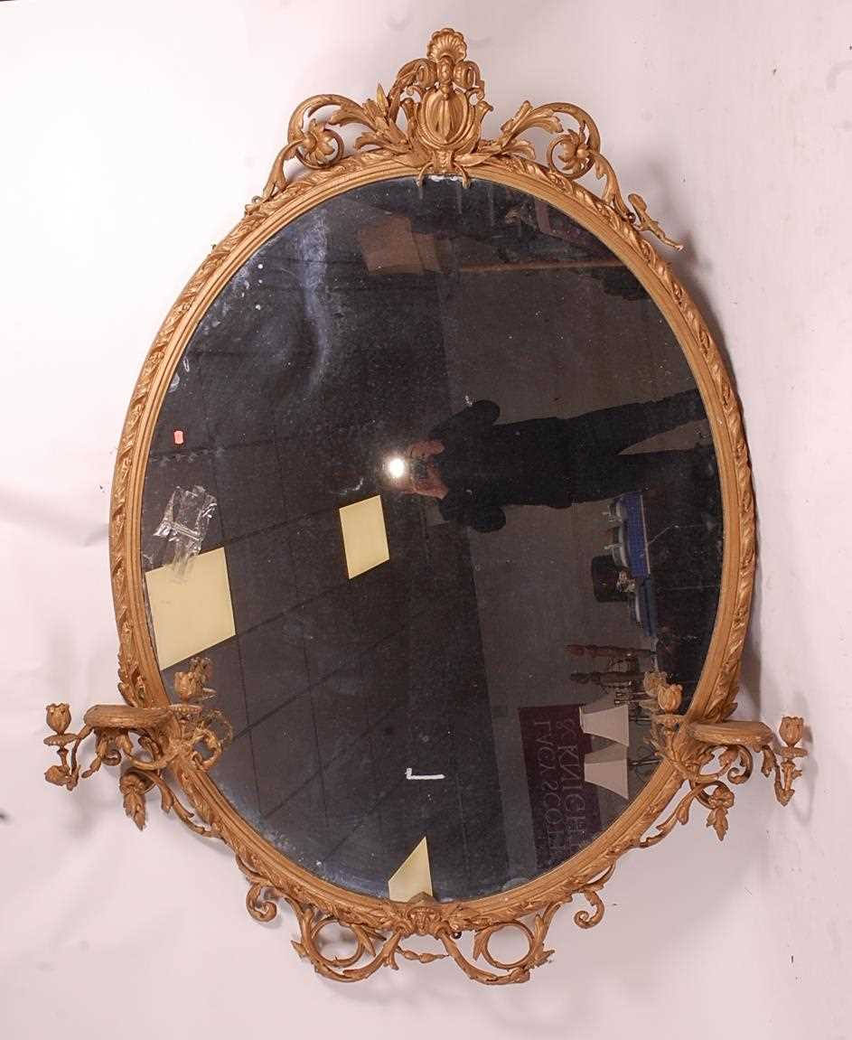 A Victorian giltwood and gesso wall mirror, of good size, the oval plate within a leaf moulded