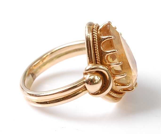 A yellow metal citrine dress ring, featuring a pear cut citrine in a claw setting, with stirrup - Image 4 of 6