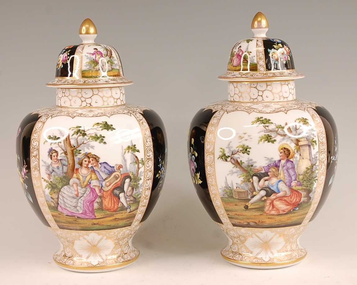 A pair of circa 1900 Dresden porcelain vases and covers, each panel decorated with alternating
