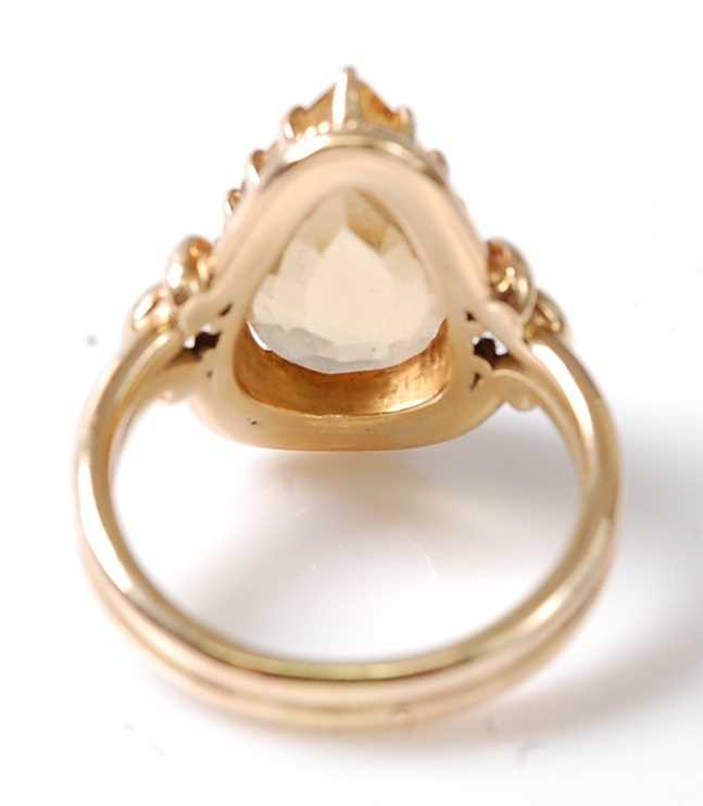 A yellow metal citrine dress ring, featuring a pear cut citrine in a claw setting, with stirrup - Image 5 of 6