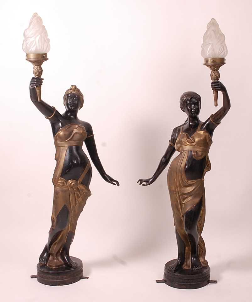 A pair of bronzed metal figurines of maidens, each holding aloft a flaming torch, in black and gilt,