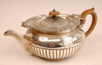 A George III silver teapot, of half-reeded circular squat form, having bright cut engraved armorial,
