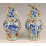A pair of 19th century Chinese stoneware celadon ground vases, each enamel decorated with exotic