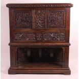 An antique joined and heavily floral relief carved oak cupboard on stand, the twin doors with