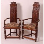 A pair of medieval style oak elbow chairs, each of triform with blind carved panel backsCondition