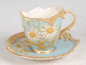 A Royal Worcester porcelain Empress teacup and saucer, shot enamel decorated with flowers and