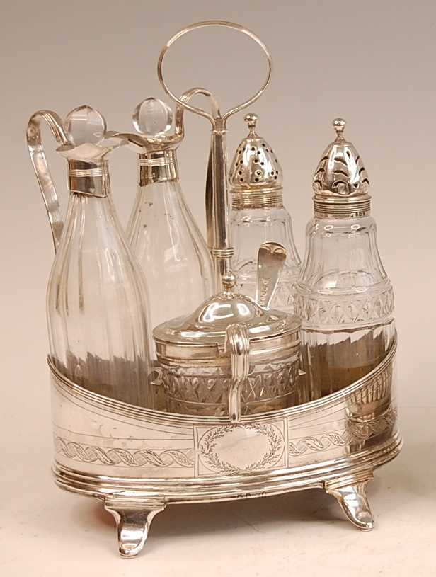 A George III silver five-bottle cruet, of oval form, with bright cut engraved decoration, comprising