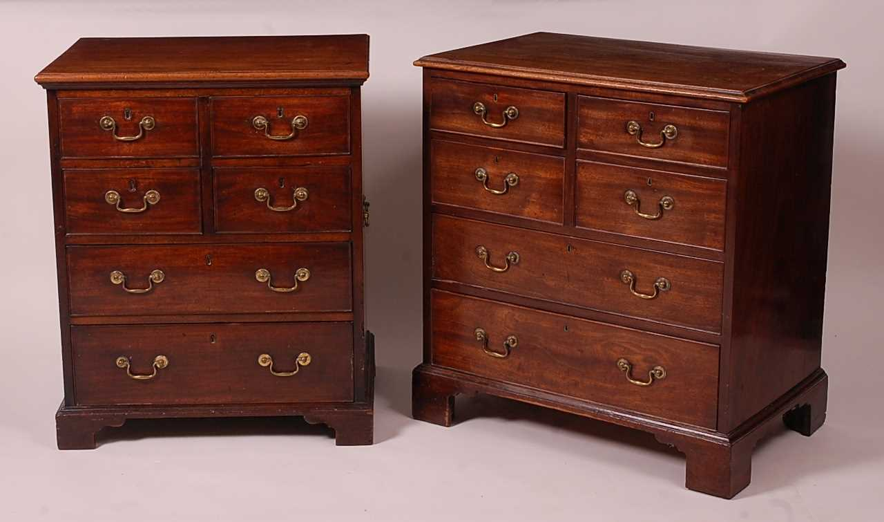 A matched pair of George III mahogany chests, each arranged as two flights of two drawers over two