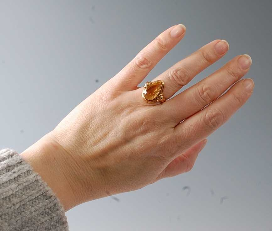 A yellow metal citrine dress ring, featuring a pear cut citrine in a claw setting, with stirrup - Image 2 of 6