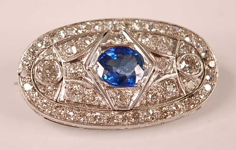 A white metal Art Deco style sapphire and diamond lozenge shaped panel brooch, featuring a centre