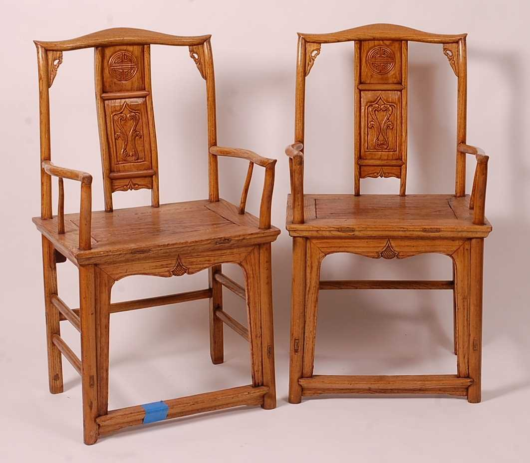 A pair of Chinese 'elm' elbow chairs, having carved splat yoke backs