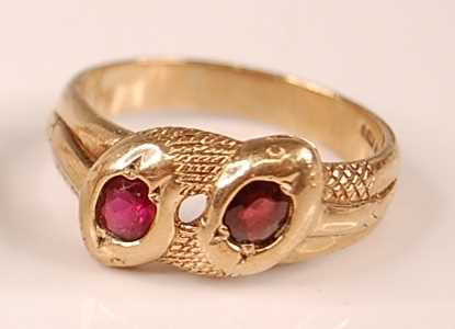 A 9ct yellow gold double-headed intertwining snake's head ring, each head set with an oval faceted