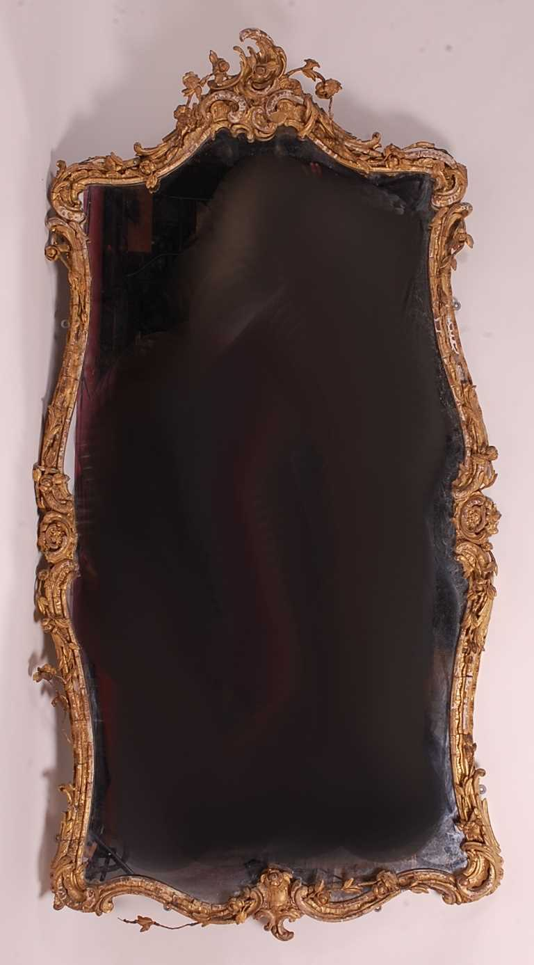 A Victorian Rococo Revival giltwood and gesso wall mirror, the shaped rectangular plate in an