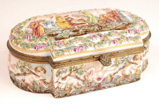 A Naples porcelain casket, having hinged cover and gilt brass mounts, the cover relief decorated