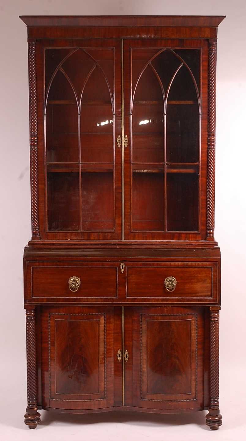 A Regency mahogany secretaire bookcase, having twin gothic arched glazed doors with enclosed