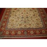 A Persian woollen cream ground carpet, decorated with scroll flowers and foliage within trailing
