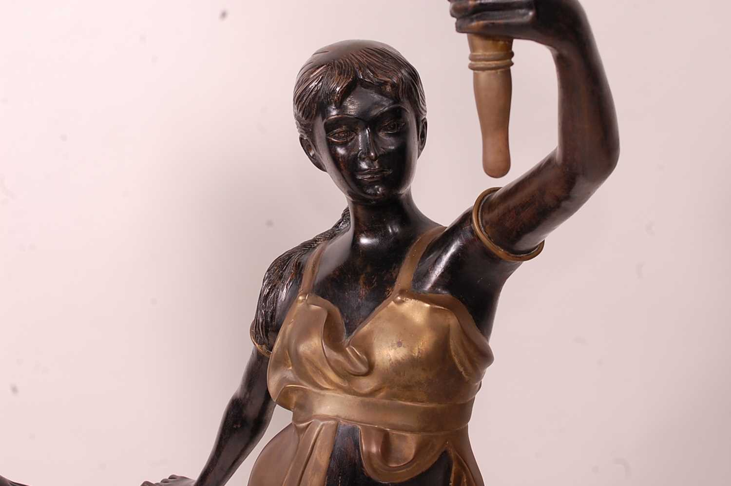 A pair of bronzed metal figurines of maidens, each holding aloft a flaming torch, in black and gilt, - Image 3 of 9